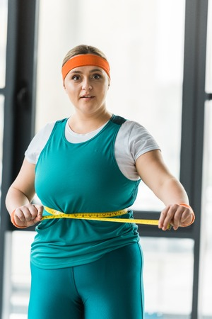 surprised plus size girl measuring waist in gym