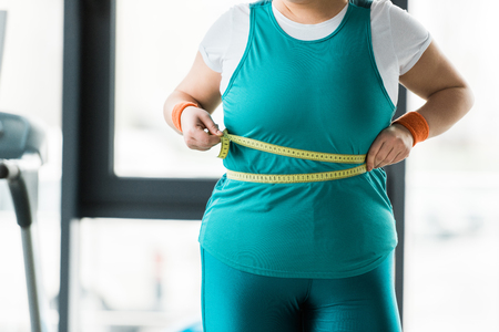 cropped view of overweight girl measuring waist in gym Stok Fotoğraf