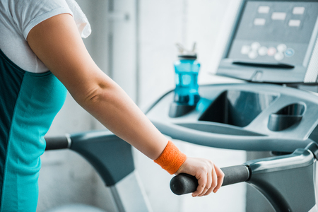 cropped view of overweight girl training on treadmill in gym
