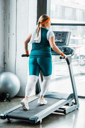 overweight girl with towel on shoulders running on treadmill in gym