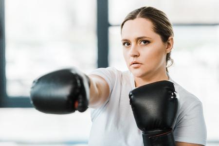 selective focus of confident overweight girl practicing kickboxing Banco de Imagens