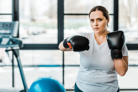serious overweight woman wearing boxing gloves practicing kickboxing in gym