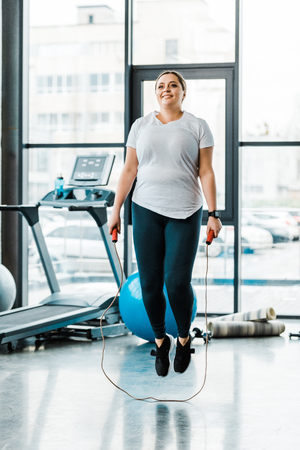 cheerful plus size woman exercising with jumping rope in gym