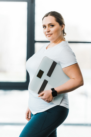 cheerful overweight woman smiling while holding scales