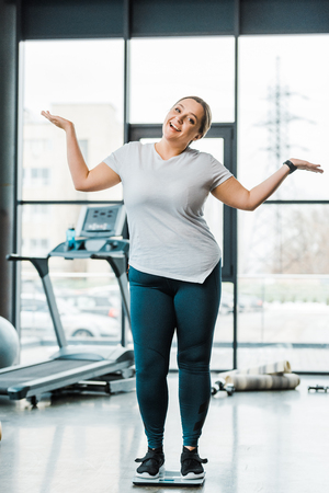 cheerful overweight woman gesturing while standing on scales