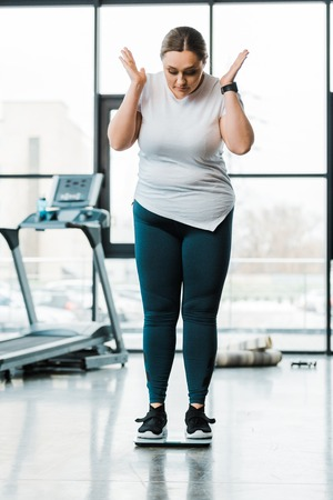 surprised overweight woman gesturing while standing on scales