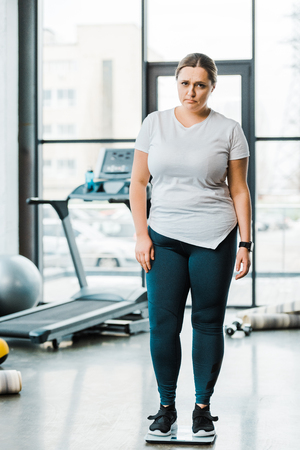upset overweight woman standing on scales in gym Stockfoto