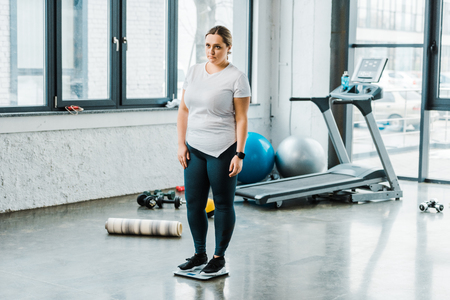 sad overweight woman standing on scales in gym Stockfoto