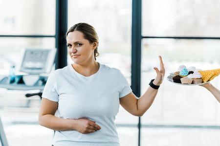 Vista recortada del hombre sujetando la placa con sabrosos pasteles cerca de la mujer con sobrepeso que no muestra signos Foto de archivo