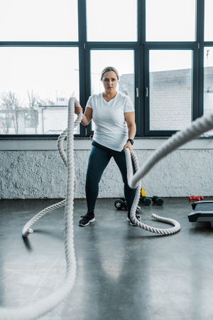 concentrated overweight woman training with battle ropes in gym