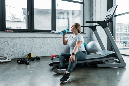 tired plus size woman sitting on treadmill and drinking water from bottle