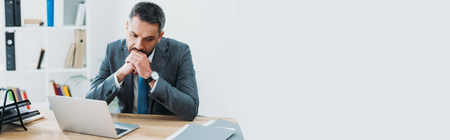 handsome businessman in grey suit sitting at table with laptop and thinking in office Banco de Imagens
