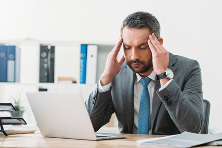handsome businessman sitting at table with laptop and feeling headache in office