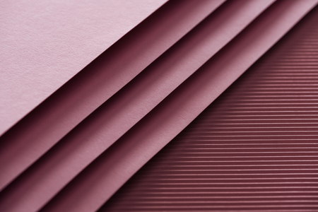 top view of blank and pink sheets of paper on burgundy background with copy space Stock Photo