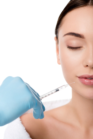 cropped view of doctor in latex glove giving lip injection with syringe to beautiful woman with eyes closed isolated on white