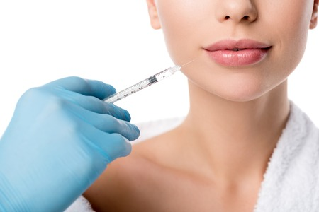 partial view of doctor in latex glove giving lip injection with syringe to woman isolated on white