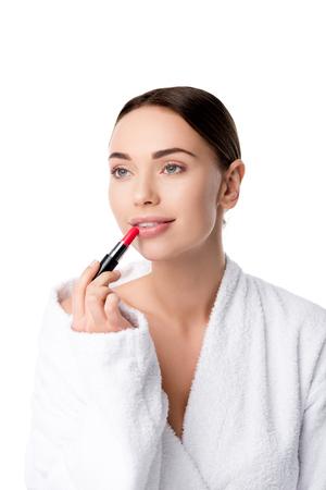 beautiful woman in bathrobe applying red lipstick isolated on white Фото со стока
