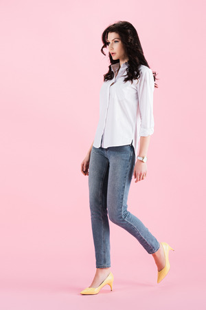 beautiful brunette girl walking in casual clothing, isolated on pink Stock Photo