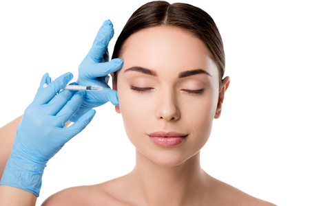 doctor in latex gloves giving beauty injection with syringe to woman with eyes closed isolated on white