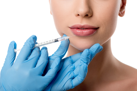 cropped view of doctor in latex gloves giving lip injection with syringe to woman isolated on white Stok Fotoğraf