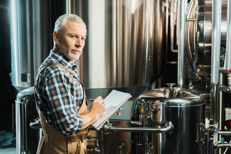 senior male brewer writing in notepad while checking brewery equipment