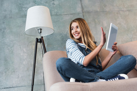 young girl smiling and turning away from monitor of digital tablet Stock Photo