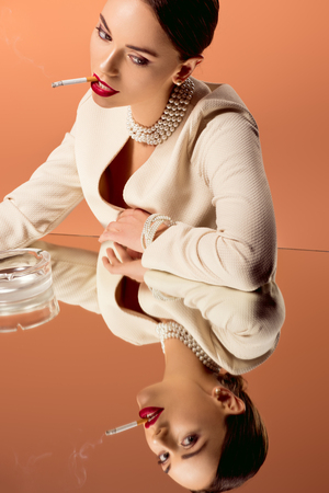 beautiful glamorous woman in pearl necklace with mirror reflection smoking cigarette isolated on orange