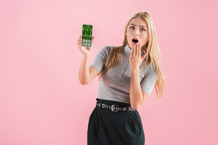 shocked woman showing smartphone with health data on screen, isolated on pink Foto de archivo - 118406634