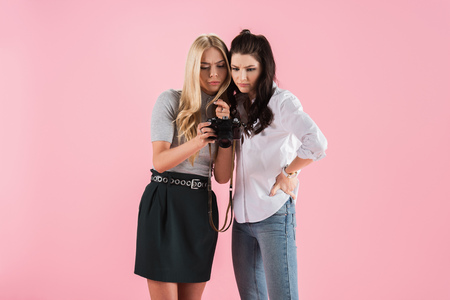 Concentrated girls watching photos on digital camera isolated on pink
