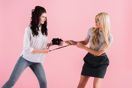 Irritated girls fighting for digital camera isolated on pink