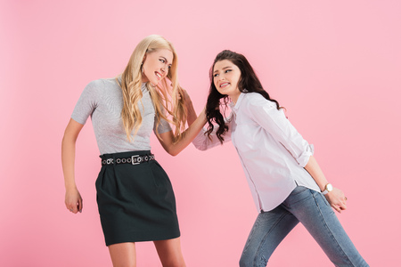 Studio shot of angry quarreling girls isolated on pink