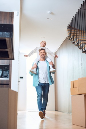happy father carrying on neck cheerful daughter in new home Фото со стока - 118407017