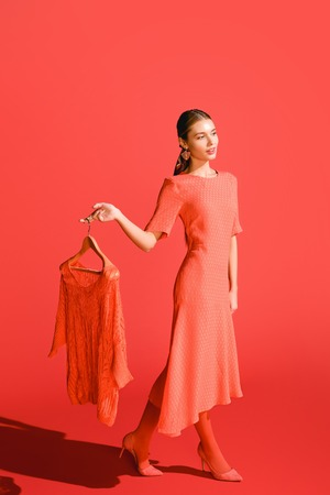attractive stylish woman holding hanger with clothing on living coral. Color of the year 2019 concept