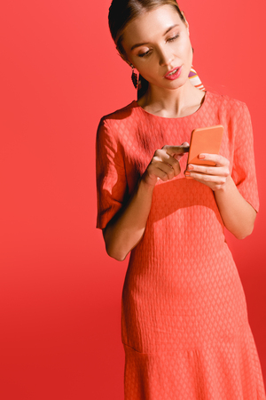 attractive woman in living coral dress using smartphone on red. Pantone color of the year 2019 concept Stock Photo