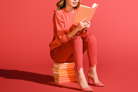 cropped view of woman reading book. Pantone color of the year 2019 concept