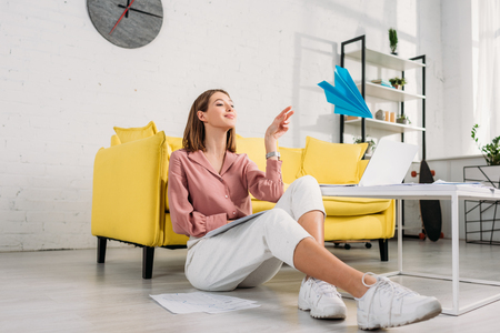 happy woman sitting on floor and playing with paper plane at home Stock Photo