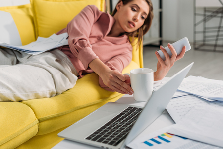 selective focus of laptop with woman using smartphone and lying on sofa on background Stock Photo