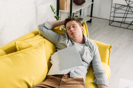 tired man sleeping on sofa with documents at home Stock Photo