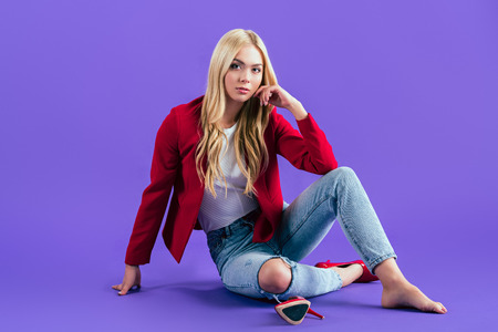 Interested young woman in red jacket sitting on floor on purple background Stock Photo