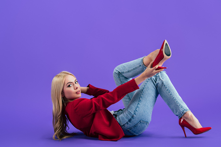 Stylish woman lying on floor and putting on high-heeled shoes on purple background