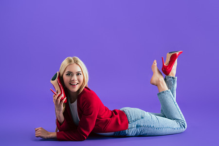 Gorgeous smiling girl in red high-heeled shoes lying on floor and looking at camera on purple background Stock Photo