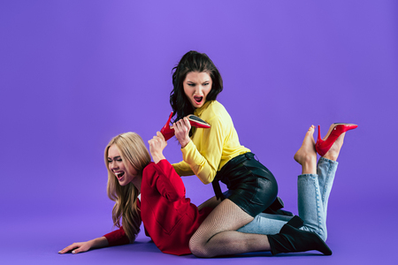 Studio shot of aggressive women yelling and fighting on floor on purple background 版權商用圖片