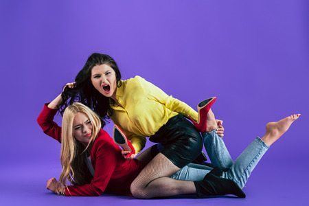 Studio shot of stylish girls screaming and fighting on floor on purple background