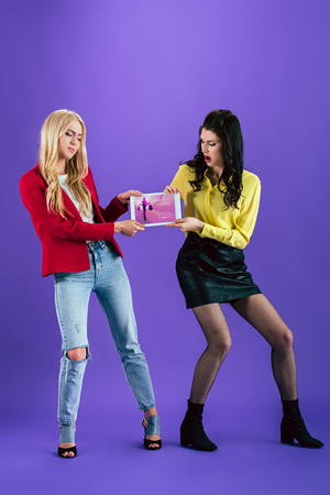 Studio shot of disgruntled girls holding digital tablet with online shopping app on screen on purple background Imagens - 118407811