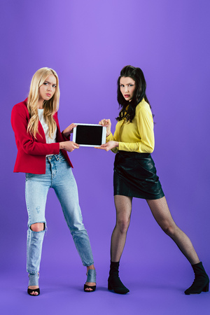 Full length view of irritated girls holding digital tablet with blank screen on purple background