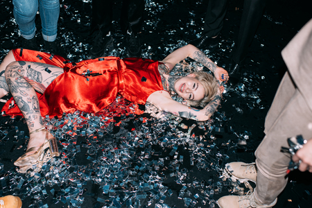 blonde woman lying on floor with confetti near people on black background