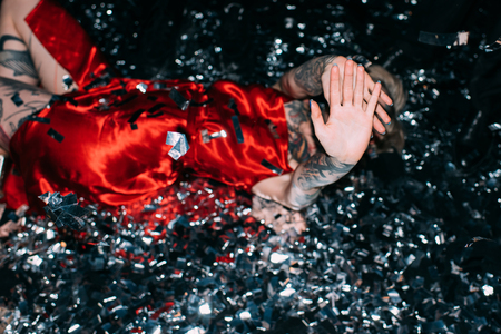drunk woman covering face while lying on floor with confetti isolated on black Stock fotó