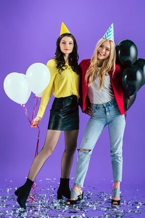 Studio shot of blissful girls in party hats holding air balloons on purple background