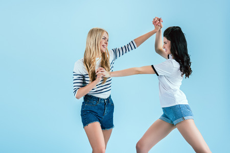 Funny girls in denim shorts fighting on blue background