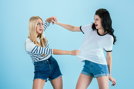 Irritated young women fighting on blue background